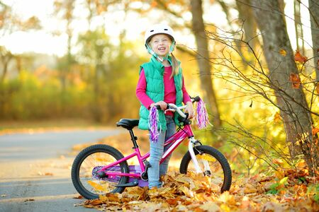 Cute little girl riding a bike in a city park on sunny autumn day. Active family leisure with kids. Child wearing safety helmet while riding a bicycle.