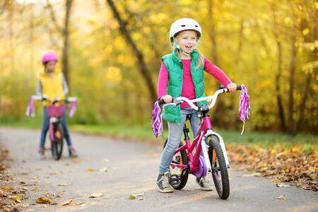 Sorelline carine che vanno in bicicletta in un parco cittadino in una soleggiata giornata autunnale. Tempo libero attivo in famiglia con bambini. Bambini che indossano il casco di sicurezza mentre vanno in bicicletta.