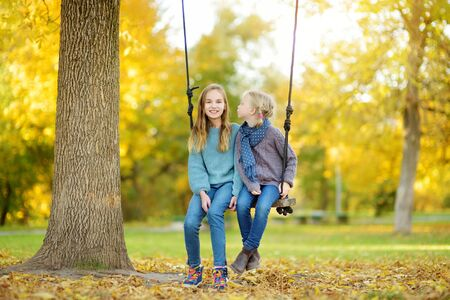 Two cute young sisters having fun on a swing in sunny autumn park. Family weekend in a city. Fall outdoor activities for children.