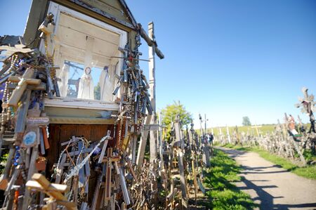 SIAULIAI, LITHUANIA - JULY 30, 2018: Various wooden crosses and crucifixes on the Hill of Crosses, a site of pilgrimage near Siauliai, Lithuania. Standard-Bild - 128986507