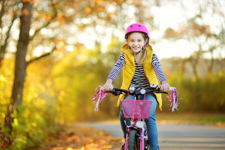 Entzückendes junges Mädchen, das an einem sonnigen Herbsttag in einem Stadtpark Fahrrad fährt. Aktive Familienfreizeit mit Kindern. Kind mit Schutzhelm beim Fahrradfahren.