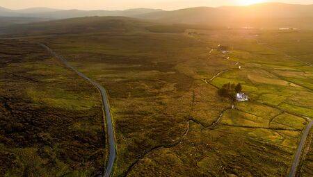 Aerial sunset view of Connemara region in Ireland. Scenic Irish countryside landscape with magnificent mountains on the horizon, County Galway, Ireland.