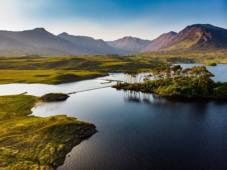 Aerial view of Twelve Pines Island, standing on a gorgeous background formed by the sharp peaks of a mountain range called Twelve Pins or Twelve Bens, Connemara, County Galway, Ireland Foto de archivo - 128290844