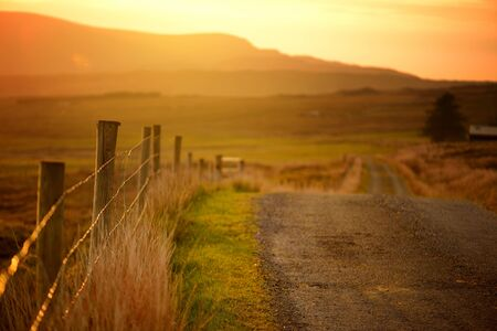 Beautiful sunset in Connemara. Scenic Irish countryside road leading towards magnificent mountains, County Galway, Ireland.