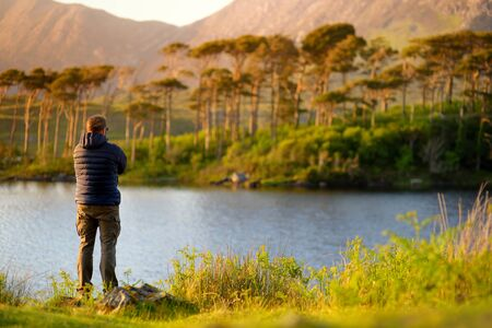 Tourist admiring the view of Twelve Pines Island, standing on a gorgeous background formed by the sharp peaks of a mountain range called Twelve Pins or Twelve Bens, Connemara, County Galway, Ireland Stockfoto