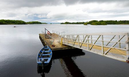 Lone boat tied to small pier on Lough Leane, the largest and northernmost of the three lakes of Killarney National Park, County Kerry, Ireland Standard-Bild - 128291195