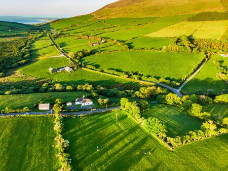 Aerial view of endless lush pastures and farmlands of Ireland. Beautiful Irish countryside with emerald green fields and meadows. Rural landscape on sunset. Standard-Bild - 128291250