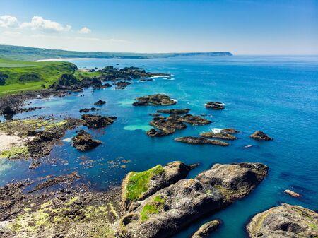Vivid emerald-green water at Ballintoy harbour along the Causeway Coast in County Antrim. Rugged coastal landscape of Northern Ireland. Standard-Bild - 128291267
