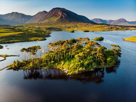Aerial view of Twelve Pines Island, standing on a gorgeous background formed by the sharp peaks of a mountain range called Twelve Pins or Twelve Bens, Connemara, County Galway, Ireland Standard-Bild - 128291271