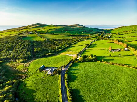 Aerial view of endless lush pastures and farmlands of Ireland. Beautiful Irish countryside with emerald green fields and meadows. Rural landscape on sunset. Standard-Bild - 128291278