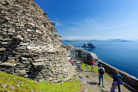 SKELLIG MICHAEL, IRELAND - MAY 22, 2018: Tourists exploring Skellig Michael, home to ruined remains of a Christian monastery, inhabited by variety of seabirds, UNESCO World Heritage Site, Ireland.