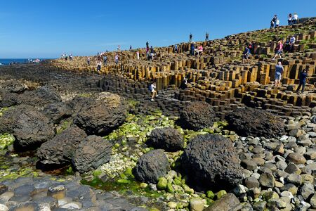 COUNTY ANTRIM, NOTHERN IRELAND - MAY 28, 2018: Tourists exploring Giants Causeway, an area of hexagonal basalt stones, created by ancient volcanic fissure eruption, County Antrim, Northern Ireland. Standard-Bild - 128986554