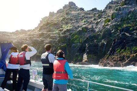 SKELLIG MICHAEL, IRELAND - MAY 22, 2018: Tourists exploring Little Skellig Island, home to many various seabirds and the second largest gannets colony in the world, County Kerry, Ireland. Standard-Bild - 128986556