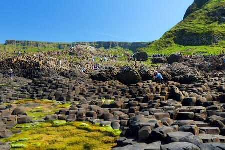 COUNTY ANTRIM, NOTHERN IRELAND - MAY 28, 2018: Tourists exploring Giants Causeway, an area of hexagonal basalt stones, created by ancient volcanic fissure eruption, County Antrim, Northern Ireland. Standard-Bild - 128986557