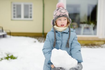 Adorable young girl building a snowman in the backyard. Cute child playing in a snow. Winter activities for family with kids.