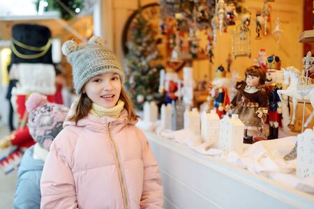 Young girl looking at Christmas dolls and decorations sold at Christmas market in Vilnius, Lithuania. Decorated and illuminated shopping stands with variety of Xmas toys. Stock Photo
