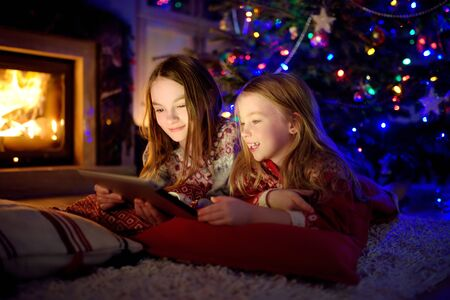 Two cute young sisters using a tablet pc at home by a fireplace in warm and cozy living room on Christmas eve. Winter evening at home with family and kids.