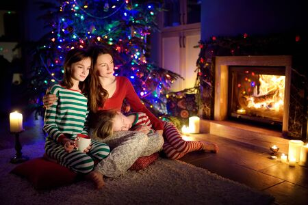 Happy young mother and her daughters having a good time sitting together by a fireplace in a cozy dark living room on Christmas eve. Celebrating Xmas at home. Winter evening with family and kids. Banque d'images