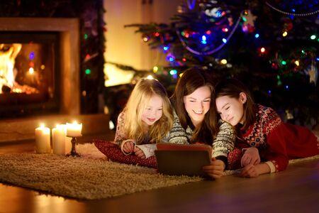 Madre y sus dos lindas hijas con un tablet pc en casa junto a una chimenea en la cálida y acogedora sala de estar en la víspera de Navidad. Noche de invierno en casa con familia y niños.