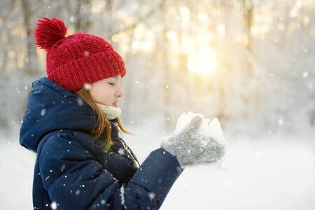 Adorable young girl having fun in beautiful winter park during snowfall. Cute child playing in a snow. Winter activities for family with kids. Banque d'images