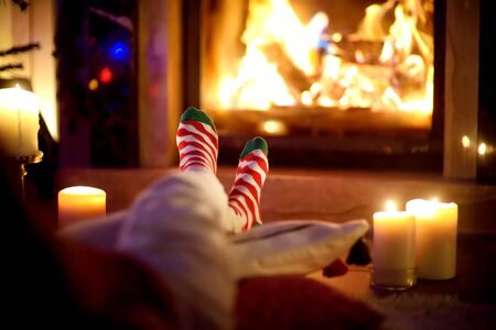 Woman resting her legs in striped festive socks in a room with a burning fireplace and candles on cozy Christmas evening. Happy festive time in winter. Imagens
