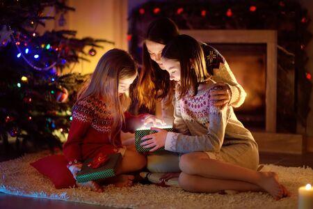 Szczęśliwa młoda mama i jej dwie córeczki otwierają w Wigilię magiczny świąteczny prezent przy kominku w przytulnym, ciemnym salonie. Zimowy wieczór w domu z rodziną i dziećmi. Zdjęcie Seryjne