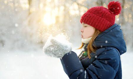 Entzückendes junges Mädchen, das sich während des Schneefalls im schönen Winterpark amüsiert. Nettes Kind, das im Schnee spielt. Winteraktivitäten für Familien mit Kindern. Standard-Bild