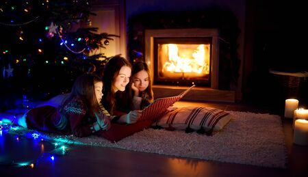 Happy young mother and her daughters reading a story book together by a fireplace in a cozy dark living room on Christmas eve. Celebrating Xmas at home. Winter evening with family and kids.