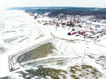 Aerial winter landscape of the Baltic Sea and frozen Curonian Lagoon near the town of Nida. Chilly winter day on the Curonian Spit in Lithuania.