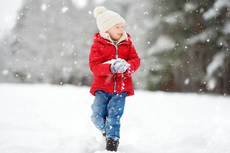 Adorable young girl having fun in beautiful winter park during snowfall. Cute child playing in a snow. Winter activities for family with kids.