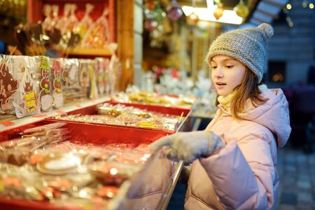 Cute young girl choosing sweets on traditional Christmas market in Riga, Latvia. Kid buying candy and cookies on Xmas. Happy family time on chilly winter day.