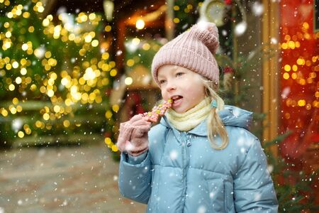 Cute young girl having gingerbread cookie on traditional Christmas fair in Riga, Latvia. Children enjoying sweets, candies and lollipops on Xmas market. Winter time with family and kids. Stock fotó