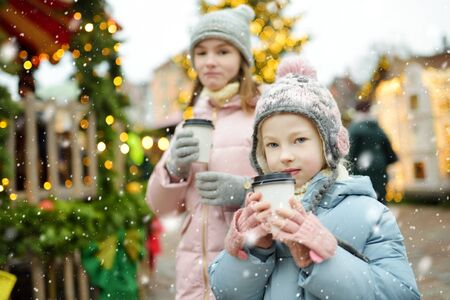 Two adorable sisters drinking hot chocolate on traditional Christmas fair in Riga, Latvia. Children enjoying sweets, candies and gingerbread on Xmas market. Winter time with family and kids.