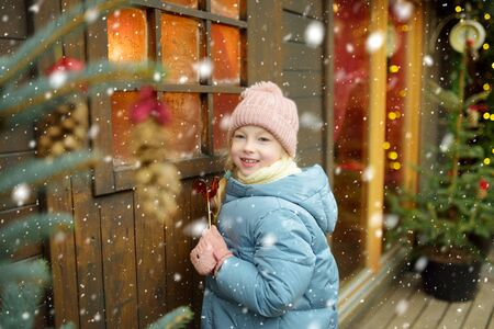 Cute young girl having rooster-shaped lollipop on traditional Christmas fair in Riga, Latvia. Child enjoying sweets, candies and gingerbread on Xmas market. Winter time with family and kids.
