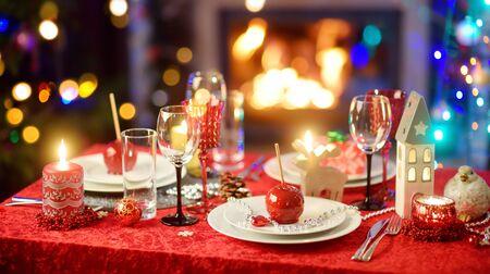 Piękne nakrycie stołu na przyjęcie bożonarodzeniowe lub obchody nowego roku w domu. Przytulny pokój z kominkiem i choinką w tle. Świąteczny czas z rodziną i przyjaciółmi.