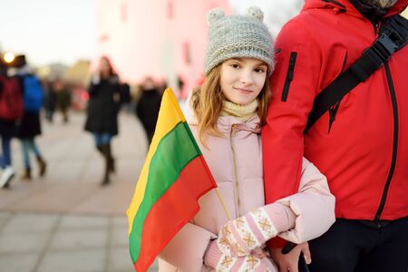 Father and daughter holding tricolor Lithuanian flag on Lithuanian Independence Day in Vilnius. Happy family celebrating national holiday.