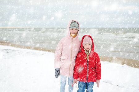 Two cute little sisters having fun together at winter beach on cold winter day. Kids playing by the ocean. Winter activities for children. Standard-Bild - 134568316