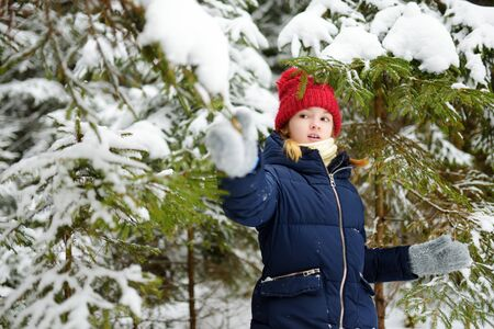 Adorable little girl having fun in beautiful winter forest. Happy child playing in a snow. Winter activities for kids.