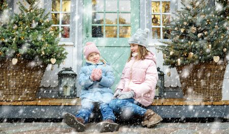 Two adorable sisters having a good time together on traditional Christmas fair in Riga, Latvia. Children enjoying sweets, candies and gingerbread on Xmas market. Winter time with family and kids. Stock fotó