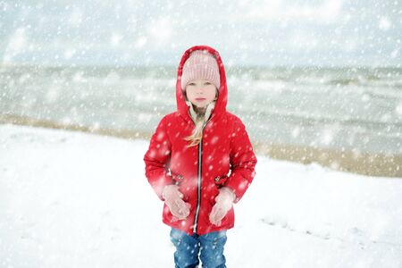 Cute little girl having fun at winter beach on cold winter day. Kids playing by the ocean. Winter activities for children. Standard-Bild - 134568403