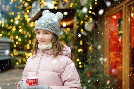 Cute young girl drinking hot chocolate on traditional Christmas fair in Riga, Latvia. Child enjoying sweets, candies and gingerbread on Xmas market. Winter time with family and kids.