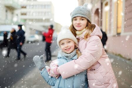 Two adorable young sisters having fun on beautiful winter day in a city. Cute children having a walk in winter town. Winter activities for kids. Banque d'images