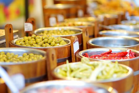 Assorted organic pickled olives, garlic, hot peppers, capers and sundried tomatos sold on a marketplace in Vilnius, Lithuania, during traditional spring fair.
