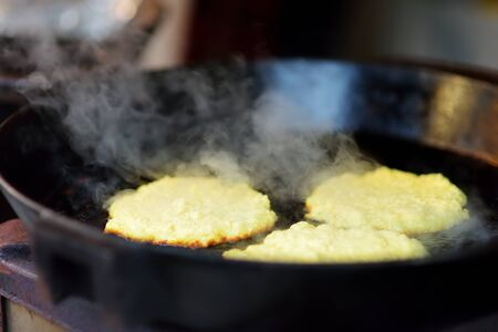 Delicious potato pancakes being fried on traditional spring market in Vilnius, Lithuania. Variety tasty street food on Easter fair. Banco de Imagens