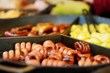 Traditional fried sausages being cooked at the spring market in Vilnius, Lithuania. Variety tasty street food on Easter fair.