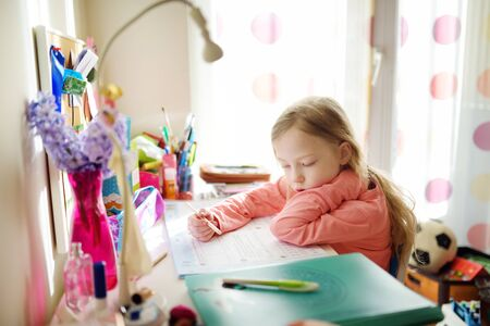 Smart little schoolgirl doing her homework at her table at home. Child learning to write and read. Education and learning for kids. Banque d'images - 140032219