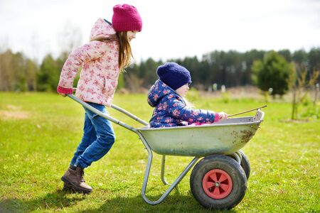 Two cute little sisters helping in a garden. Children taking part in outdoor household chores. Active family leisure at spring.