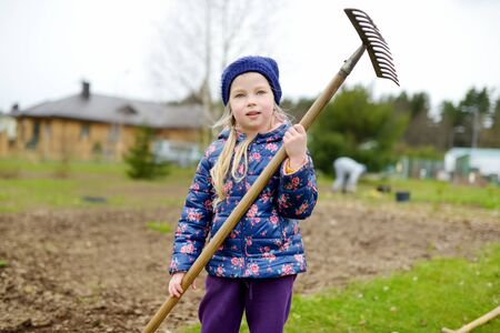 Cute little girl helping in a garden. Child taking part in outdoor household chores. Active family leisure at spring.