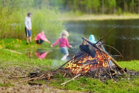 Forest bonfire. Having fun at a camp site with family and friends. Fun activities in summer.