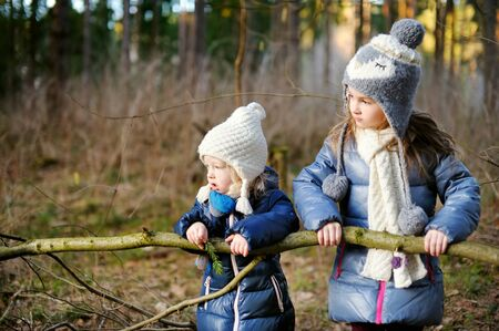 Cute little girls having fun during forest hike on beautiful spring day. Children exploring wild nature. Active family leisure with kids.